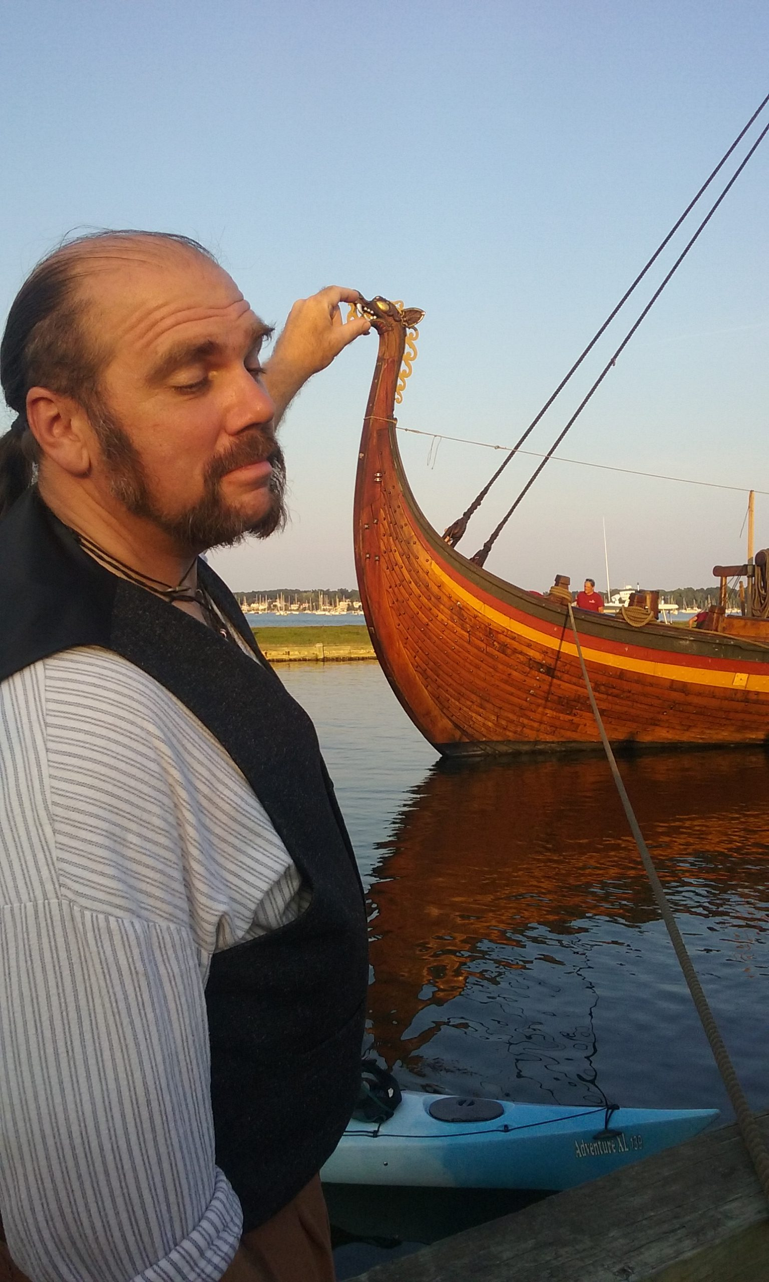 Chris Dowgin squeezing the head of a Dragon prow on a Viking longship