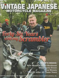 Gerald Dowgin on 65 Honda Scrambler for the cover of Vintage Japanese Motorcycle Magazine at a car show.