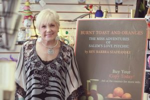 Rev Barbara the Salem Love Psychic and author of the Corona Virus Horoscope stands in front of poster for her book Burnt Toast and Oranges.